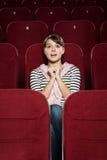 Emotionell flicka som håller ögonen på en film Arkivfoton