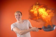 Emotionell grabb som rymmer en stekpanna i hans händer, på en orange bakgrund royaltyfri foto