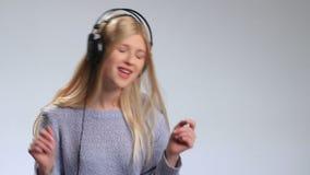 Emotionell kvinna med hörlurar som lyssnar till musik stock video
