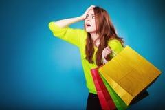 Emotionell kvinna med pappers- shoppingpåsar på blått Arkivfoton
