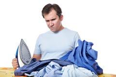 Emotionell man med en hög av tvätterit, innan isolerat att stryka royaltyfria foton