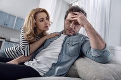 Emotionell man som trycker på hans panna medan hans snälla fru som nära sitter Arkivbilder