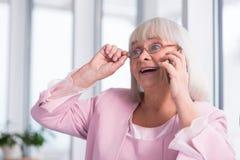 Emotionell mogen kvinna som talar till någon på telefonen Royaltyfri Fotografi