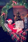 Emotionell nätt flicka på en gunga från julgranfilialerna på bakgrunden av en spis i nytt års rum med th royaltyfri fotografi