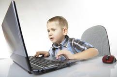 Emotionell pojke för datorböjelse med bärbara datorn Arkivfoto