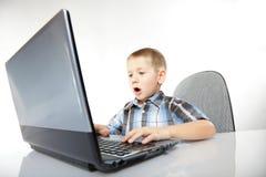 Emotionell pojke för datorböjelse med bärbara datorn Royaltyfria Foton