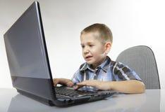 Emotionell pojke för datorböjelse med bärbara datorn Royaltyfri Bild