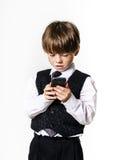 Emotionell rödhårig pojke med mobiltelefonen Royaltyfri Fotografi