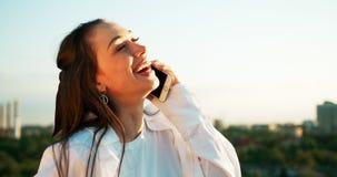 Emotionell sidostående av den unga charmiga kvinnan med naturligt smink och älskvärt leende som talar via mobiltelefonen arkivfilmer