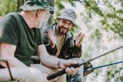 Emotionell skäggig man som fiskar med hans äldre fader arkivfoton