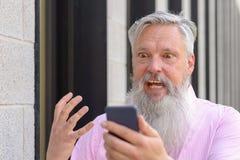 Emotionell skäggig man som ser hans mobil arkivfoton