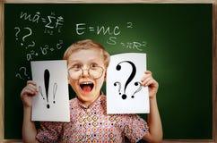 Emotionell skrikig elevpojke nära den svart tavlan Fotografering för Bildbyråer