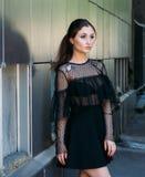 Emotionell stående av den stilfulla ståenden för mode av den nätta unga kvinnan stadsstående SAD flicka Brunett i en svart klänni Royaltyfri Foto