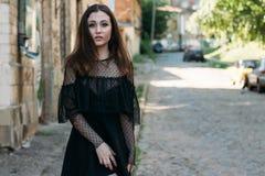 Emotionell stående av den stilfulla ståenden för mode av den nätta unga kvinnan stadsstående SAD flicka Brunett i en svart klänni Royaltyfri Fotografi