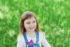 Emotionell stående för Closeup av den gulliga lilla flickan med leendeanseende på en grön äng royaltyfri bild