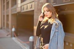 Emotionell stilfull stående av en ung blond kvinna på en cityscapebakgrundsnärbild i inställningssolen fotografering för bildbyråer