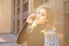 Emotionell stilfull st?ende av en ung blond kvinna p? en cityscapebakgrundsn?rbild i inst?llningssolen arkivfoto