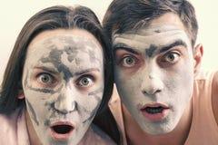 Emotionell stor stående av ett gift par i maskeringar för framsidan av lera dag Spa, Wellness, skincare royaltyfri foto