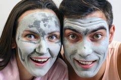 Emotionell stor stående av ett gift par i maskeringar för framsidan av lera dag Spa, Wellness, skincare royaltyfria foton