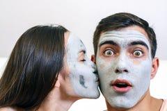 Emotionell stor stående av ett gift par i maskeringar för framsidan av lera dag Spa, Wellness, skincare arkivbild