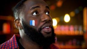 Emotionell svart man med hopp i ögon och fransk flagga på hållande ögonen på strid för kind royaltyfri bild