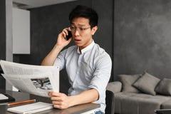 Emotionell ung asiatisk man som talar vid telefonen royaltyfri foto