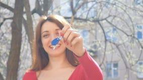 Emotionell ung flicka som rymmer tangenter med blå keychain med lycka och excitings Kvinnlig hand med det röda manikyrinnehavet arkivfilmer