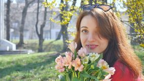 Emotionell ung kvinna med solglasögon som utanför står med en stor bukett av färgrika blommor och ler under tidigt lager videofilmer