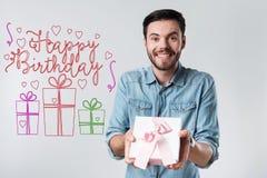 Emotionell ung man som rymmer en gåva, medan vara på födelsedagpartiet arkivfoto