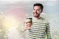 Emotionell ung man som ser upphetsad, medan rymma en kopp kaffe Royaltyfria Bilder