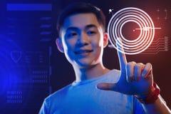 Emotionell ung man som trycker på hologrammet som aktiverar systemet Arkivbild