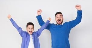 Emotionell upphetsad fader och son som hurrar för seger arkivbild