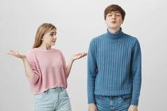 Emotionella caucasian par Den unga manliga tröjan för iklädda blått trutar kanter, överför kyssar till kameran, medan hans flickv Arkivbilder