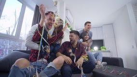Emotionella fotbollsfanvänner som håller ögonen på sportar, spelar på television hemma och jublar om favorit- lagseger stock video
