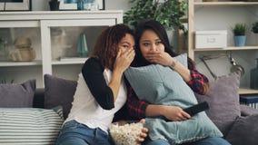 Emotionella unga kvinnor håller ögonen på rysaren tillsammans att dölja bak kuddar och stängande ögon Flickor äter popcorn arkivfilmer
