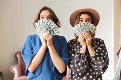 Emotionella unga kvinnor som rymmer inomhus pengar Arkivfoto