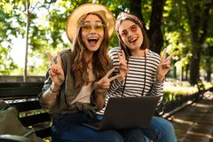 Emotionella upphetsade lyckliga damvänner som sitter utomhus genom att använda gest för fred för bärbar datordatorvisning arkivfoton