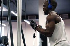 Emotionellt foto av en svart muskulös man i en T-tröja och hörlurar som skakar händer med en simulator i idrottshallen arkivbild