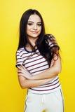 Emotionellt posera för ung nätt tonårs- kvinna på gul bakgrund, begrepp för modelivsstilfolk royaltyfria bilder