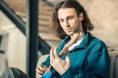 Emotionless long-haired unusual guy starting his musical repetition. Musical instrument. Emotionless long-haired unusual guy starting his musical repetition royalty free stock photo