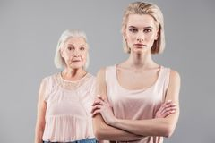 Emotionless young girl with blonde hair categorically standing stock image