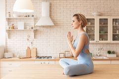 Calm and tranquil short-haired woman sitting in lotus posture on kitchen table stock photos