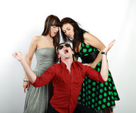 Emotions. Attractive emotional young man between two girls royalty free stock photography