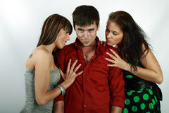 Emotions. Attractive emotional young man between two girls royalty free stock image