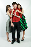 Emotions. Attractive emotional young man between two girls stock image