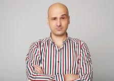 Emotions of bald man. Confused middle aged guy wearing shirt isolated over grey studio wall Stock Photography