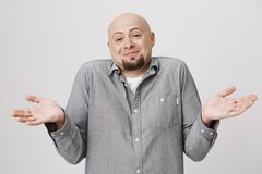 Emotions and body language concept. Good looking happy bald man with beard shrugging and over white wall. Male is. Perplexed but looks to be in good mood Stock Image
