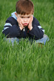 Emotions of the child. Which sits in a green grass Royalty Free Stock Photo