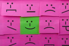 Emotions concept. Background of Sticky Notes. Green sticky note is among pink sticky notes royalty free stock images