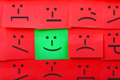 Emotions concept. Background of Sticky Notes. Green sticky note is among red sticky notes royalty free stock photo